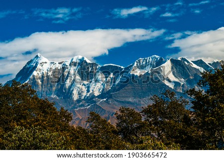 Mountains in the snow. Landscape with clouds. Scenic view of Himalayan ranges. Landscape with trees and sky, clouds and mountains. Scenic mystic view of Himalaya on trek, Bramhatal, Lohjung Royalty-Free Stock Photo #1903665472