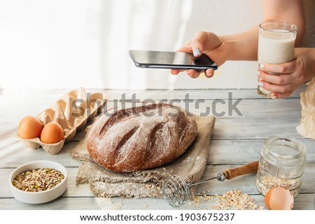 unrecognizable person takes pictures of cooking homemade food on smart phone. homemade baked grain bread with seeds. kitchen table with eggs, flour and pastries. food blogging, online cooking at home