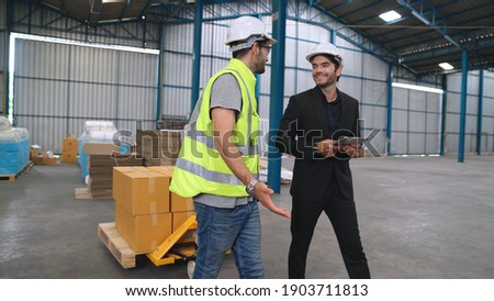 Factory workers deliver boxes package on a pushing trolley in the warehouse . Industry supply chain management concept . Royalty-Free Stock Photo #1903711813