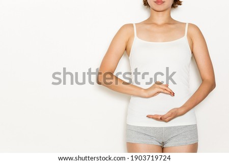 A woman has her hand on her stomach. Royalty-Free Stock Photo #1903719724