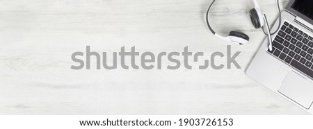 Laptop. keyboard and headphones on grey desk and plain wooden background wide banner. Helpdesk or call center headset. Distant learning or working from home, online courses or support center concept. Royalty-Free Stock Photo #1903726153