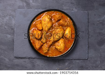 Chicken curry or masala,Kerala style chicken curry using fried coconut in traditional way and arranged in a black  ceramic vessel which is placed on a graphite sheet with grey background,isolated. Royalty-Free Stock Photo #1903754356