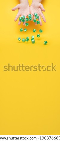 A lot of green dice fall from the hands on a yellow background: board games, selective focus on the hands, a photo in motion, vertical banner with space for text