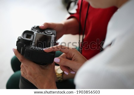 Two women hold camera in their hands. Online courses for beginner photographers concept
