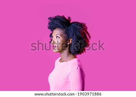 Young beautiful black woman on profile staring serene looking up serious isolated on pink background Royalty-Free Stock Photo #1903971886