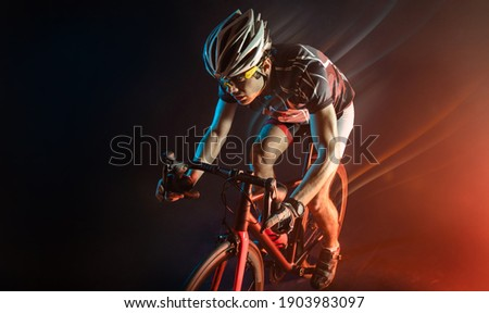 Sport. Athlete cyclists in silhouettes on dark background Royalty-Free Stock Photo #1903983097