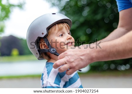 Father puts a safety helmet on little smiling boy for scooter  Royalty-Free Stock Photo #1904027254