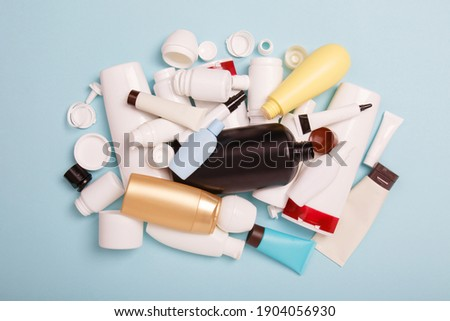 heap of separate collection of HDPE bottles from cosmetics for recycling. High-Density Polyethylene recyclable cosmetics package on blue background. Plastic garbage. Save the planet Royalty-Free Stock Photo #1904056930