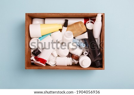 heap of separate collection of HDPE bottles from cosmetics for recycling. High-Density Polyethylene recyclable cosmetics package in a wooden box on blue background. Plastic garbage. Save the planet Royalty-Free Stock Photo #1904056936