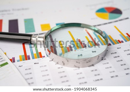 Magnifying glass on charts graphs paper. Financial development, Banking Account, Statistics, Investment Analytic research data economy, Stock exchange trading, Business office company meeting concept. Royalty-Free Stock Photo #1904068345