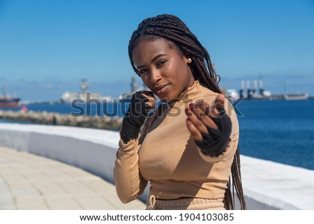 Portrait of beautiful young afro american woman looking at camera, with bandages on her hands to practice martial arts, boxing. Sky and sea background, seafront. Royalty-Free Stock Photo #1904103085