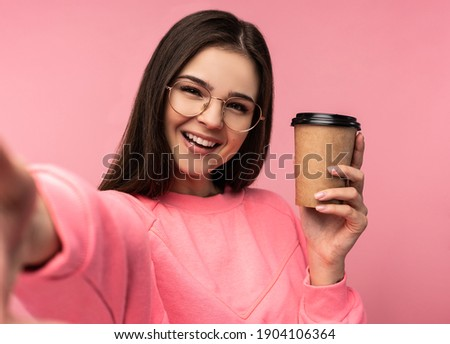 Photo of attractive woman in glasses holds coffee and takes selfie. Student wears casual pink t-shirt white pants isolated pink color background