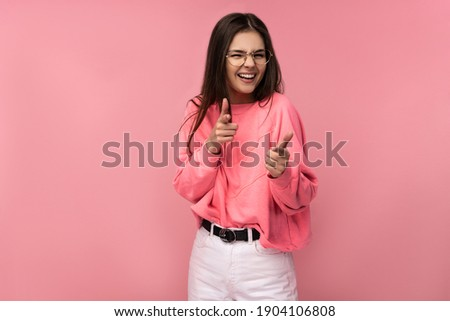 Photo of attractive young woman in glasses smiles and snaps fingers. Wears casual pink t-shirt white pants isolated pink color background