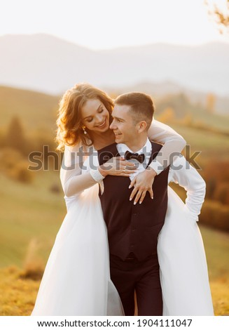 The groom carries his bride on his shoulders on the hills at sunset.