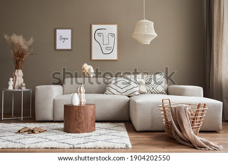 Interior design of stylish living room with modern neutral sofa, mock up poster farmes, dried flowers in vase, coffee tables, decoration and elegant personal accessories in home decor. Template.
