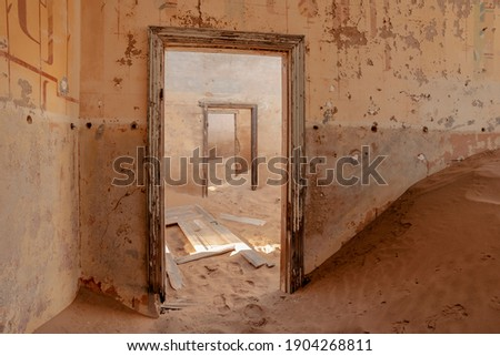 view through ruined doorways in abandoned house in Kolmanskop town, Namibia