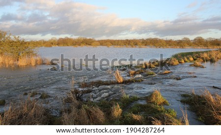 Flooding, a river bursting its banks Royalty-Free Stock Photo #1904287264