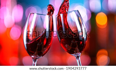 Red Wine Glasses Hitting Together in a Bar, Cheers Concept. Royalty-Free Stock Photo #1904293777