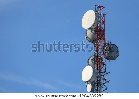The upper portion of a communications tower holds an array of several microwave backhaul antennas with protective radome covers, giving them the appearance of a bass drum. Royalty-Free Stock Photo #1904385289