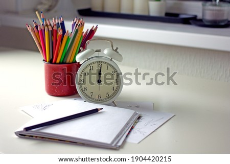 Colored pencils in a red glass, an alarm clock and a sketchbook on a white table against the background of a window. Home hobbies authentic drawing. Hobby background Royalty-Free Stock Photo #1904420215
