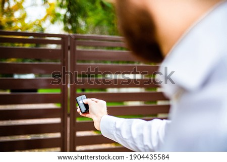 A male hand holding a remote control to open an entrance gate. An automatic opening, closing of a driveway gate. A modern house. Royalty-Free Stock Photo #1904435584