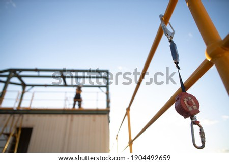 Safe work practices an inertia reel shock absorbing fall protection hook lanyard device clipping hanging on handrail with defocused construction worker working at heights in fall restraint background Royalty-Free Stock Photo #1904492659