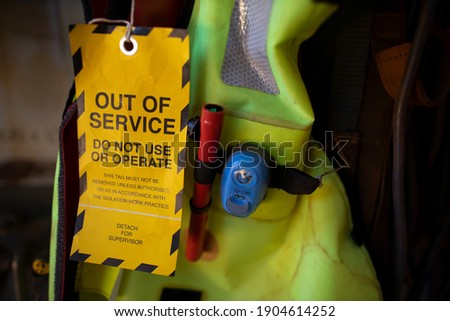 Safe workplaces yellow out of service tag warning sign hanging on damage faulty placing on boat marine safety personal floatation device equipment   Royalty-Free Stock Photo #1904614252