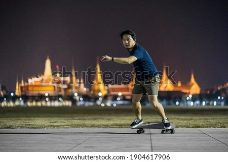 Asian Cheerful man playing surfskate or skate board in outdoor Park at night over photo blur of Bangkok Grand Palace,Thailand, low light, extream sport, healthy and exercise,fashion in covid19 concept