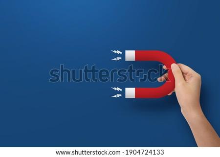 Close up of hand holding horseshoe magnet at blue background.