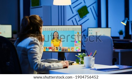 Freelancer retoucher woman working overtime on laptop computer with photo editing software. Professional graphic editor retouching photos of a client during night time in home office on performance pc