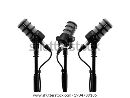 Three podcast microphones on a tripod, a black metal dynamic microphone on an isolated white background, for recording podcast or radio program, show, sound and audio equipment, technology, Photo, DJ
