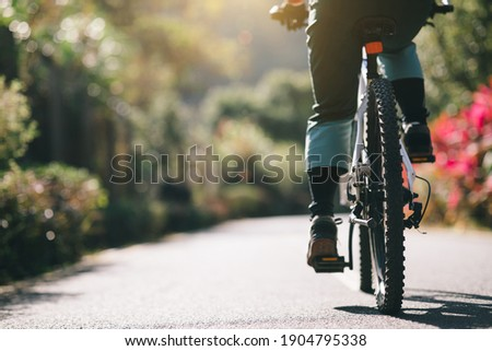Woman riding a bike on tropical park trail in spring Royalty-Free Stock Photo #1904795338