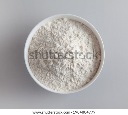 bowl of flour on grey kitchen table background, top view, selective focus Royalty-Free Stock Photo #1904804779