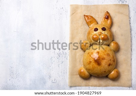 Homemade Easter Baking. Easter Bunny Bun on light gray textured background, flat lay, space Royalty-Free Stock Photo #1904827969