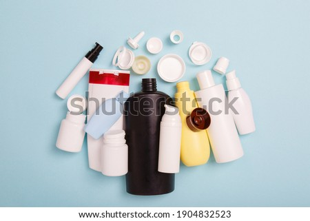 separate collection of sorted HDPE bottles from cosmetics for recycling. High-Density Polyethylene recyclable cosmetics package on blue background. Plastic garbage. Save the planet Royalty-Free Stock Photo #1904832523
