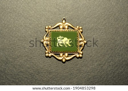 Pendant with vintage ornament golden taurus on the basis of green malachite on a black background