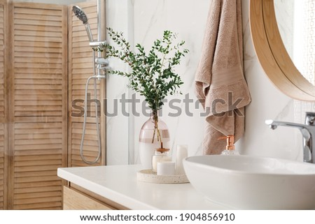 Vase with beautiful branches, candles and toiletries near vessel sink in bathroom. Interior design Royalty-Free Stock Photo #1904856910