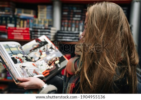 A beautiful woman in a book store holds an open comic book in the ruffs (the book is blurred). Royalty-Free Stock Photo #1904955136