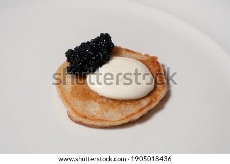 One Black Caviar Blini Buckwheat Pancake with Sour Cream on a White Plate Royalty-Free Stock Photo #1905018436