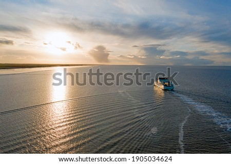Aerial from the ferry from Ameland arriving at Holwerd in the Netherlands at sunset Royalty-Free Stock Photo #1905034624