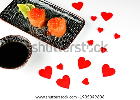 St valentines dinner for lovers. Red hearts with sushi rolls with salmon avocado and caviar on the white background. sushi rolls for celebration of 14 february. love sushi concept