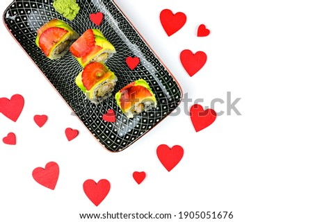 sushi rolls with salmon avocado and strawberry isolated with red hearts. St valentines greeting card. love food background. love sushi rolls concept. St valentines dinner.