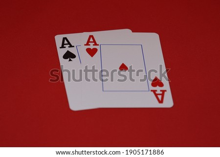 a pair of aces for a poker game on a red background