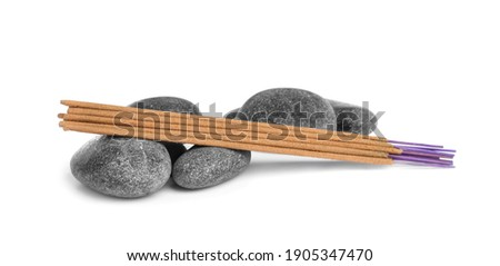 Aromatic incense sticks and spa stones on white background Royalty-Free Stock Photo #1905347470