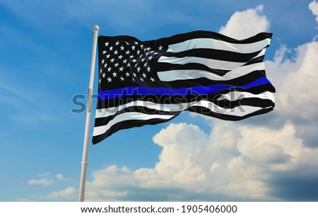 Thin Blue Line. Black Flag of USA with Police Blue Line waving in the wind on flagpole against the sky with clouds on sunny day Royalty-Free Stock Photo #1905406000
