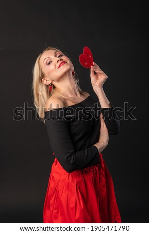 Girl holding a heart at the level of eyes Valentine symbol, heart , on the floor of hearts is married to the space. the honeymoon form. Copy of space forever, hearts in red dress girl, barefoot