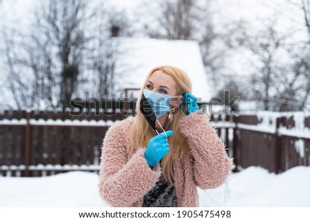double mask. a young woman puts on the first mask with her left hand behind her ear and holds the second mask with her right hand. hands in medical gloves Royalty-Free Stock Photo #1905475498
