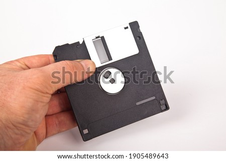 Old computer and data storage technology, hand held black plastic magnetic floppy disk 3½ inches, isolated on white background