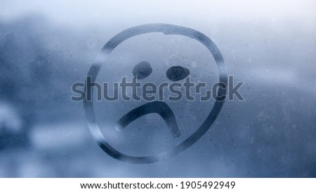 Hand drawn sad emoji on foggy glass window background. Unhappy face sign close-up. Selective focus on photo. Depression and sadness concept.