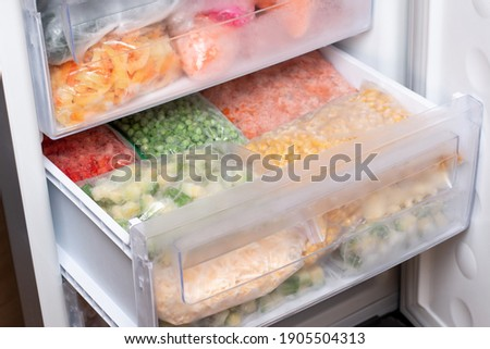 Plastic bags with different frozen vegetables in refrigerator. Food storage Royalty-Free Stock Photo #1905504313